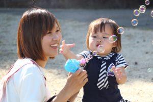 シャボン玉をする先生と幼児